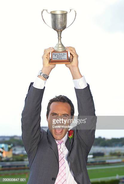 Young man in suit holding up racing trophy, cheering, portrait