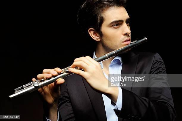 Junger Mann spielt Flöte