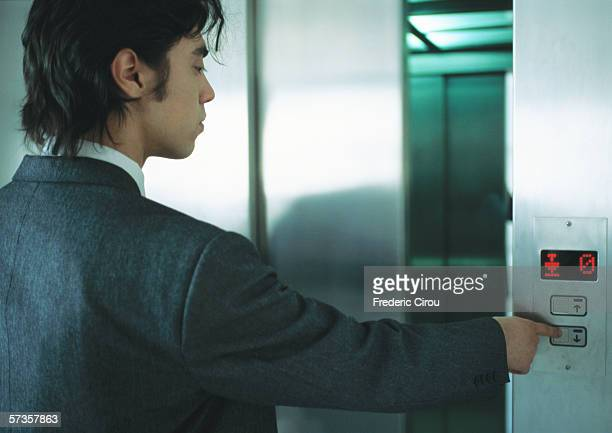 Young man in suit pushing button for elevator