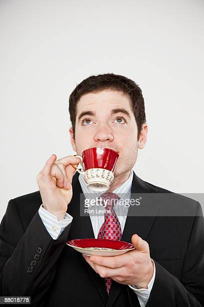 Young man in suit sipping tea
