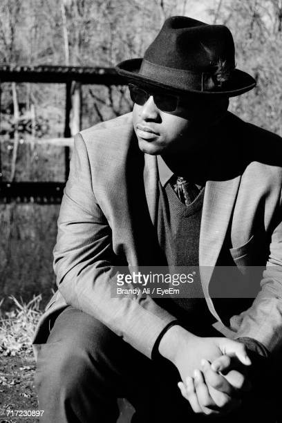 Young Man In Suit Sitting At Lakeshore