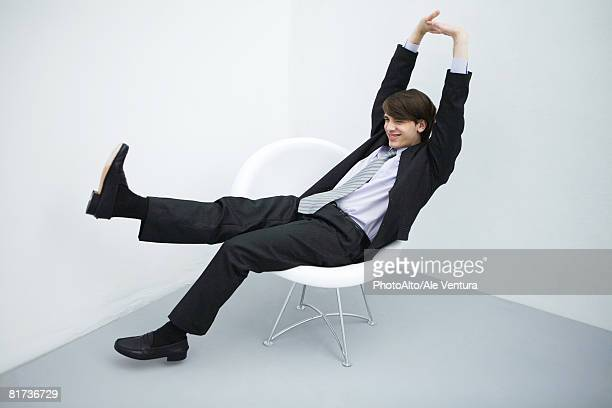 Young man in suit sitting in chair, legs outstretched, arms raised, full length