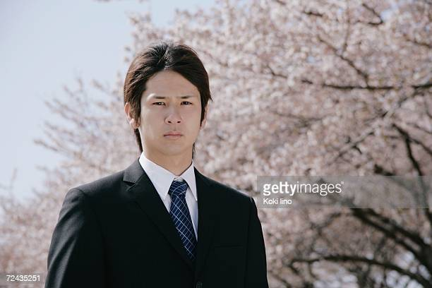 A young man in suit standing in front of cherry blossoms