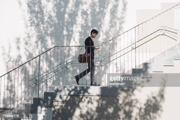 young man in suit walking on stairs and looking at cell phone - degraus e escadas - fotografias e filmes do acervo