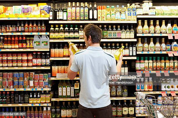 young man in supermarket comparing bottles of oil, rear view, close-up - beslissingen stockfoto's en -beelden