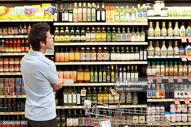 Young man in supermarket looking at bottles on shelves, close-up