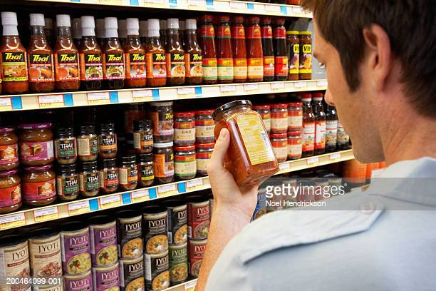 Young man in supermarket reading jar label, rear view, close-up