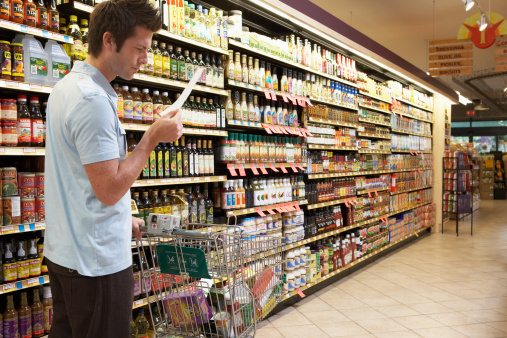 Young man in supermarket reading shopping list, side view - gettyimageskorea