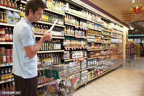 Young man in supermarket reading shopping list, side view