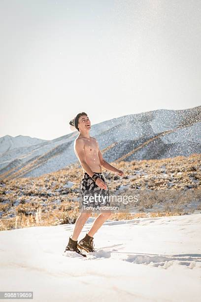 young man in swim suit playing in snowy field - halbbekleidet stock-fotos und bilder