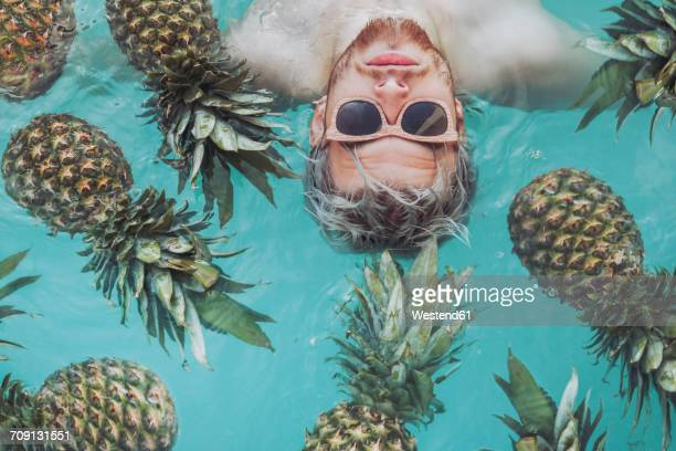 Young man in swiming pool surrounded by pineapples