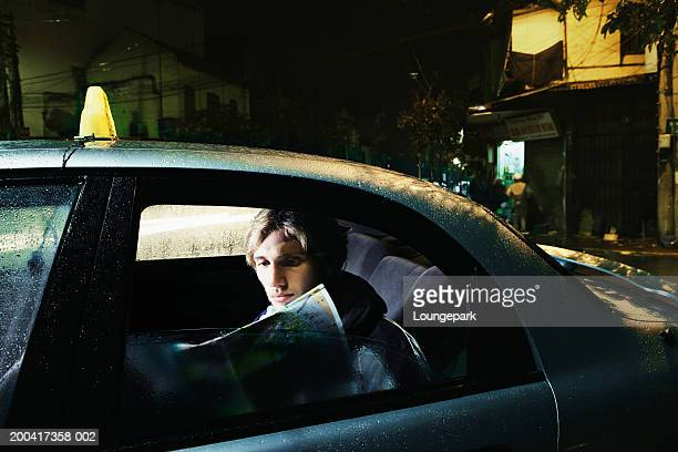Young man in taxi looking at map, view through open window, night