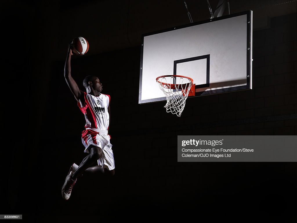 Young man in the air about to dunk the basketball : Stock Photo