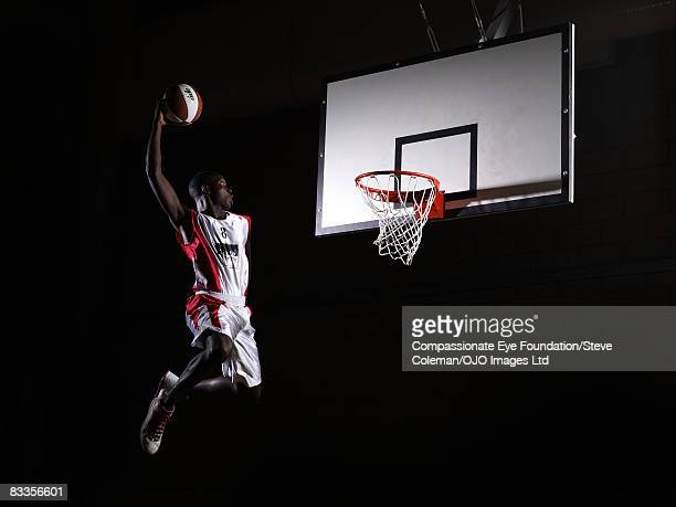 young man in the air about to dunk the basketball - basketball stock-fotos und bilder