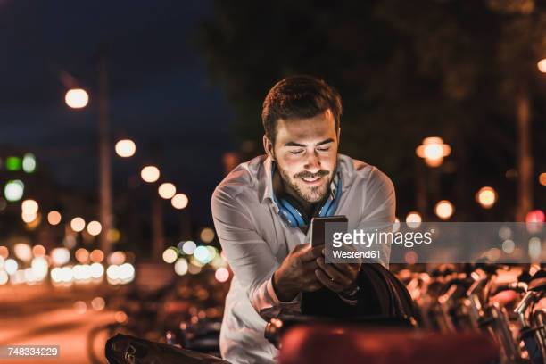 young man in the city checking cell phone at night - abenddämmerung stock-fotos und bilder