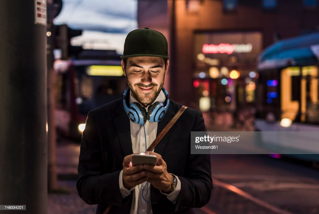 Young man in the city checking cell phone in the evening : ストックフォト