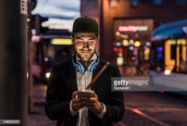 young man in the city checking cell phone in the evening - unterwegs stock-fotos und bilder