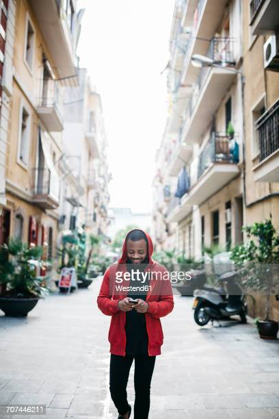 young man in the city checking cell phone - black alley stock photos and pictures