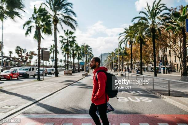 Young man in the city crossing the street