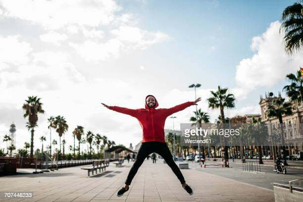 young man in the city jumping on pavement - black jacket stock photos and pictures