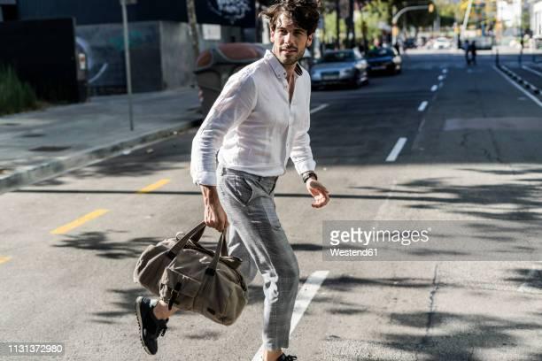 young man in the city on the go crossing street - cruzar fotografías e imágenes de stock