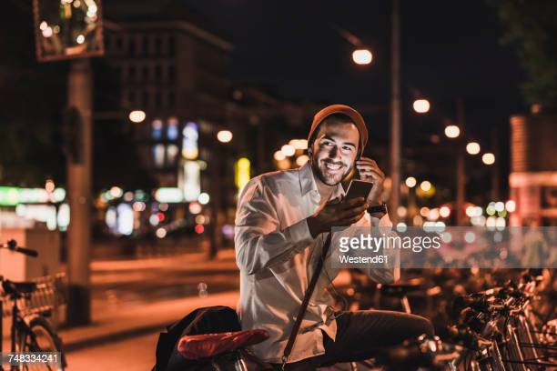 Young man in the city with eardphones and cell phone at night