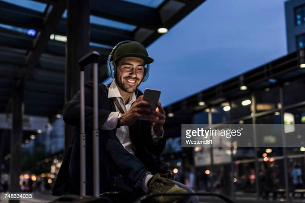 young man in the city with headphones and cell phone in the evening - station stock pictures, royalty-free photos & images