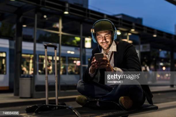 Young man in the city with headphones and cell phone in the evening
