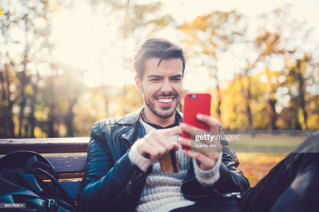 Young man in the park shopping online : Stock Photo