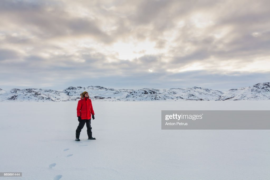 Young man in the snowy tundra at sunset : Stock Photo