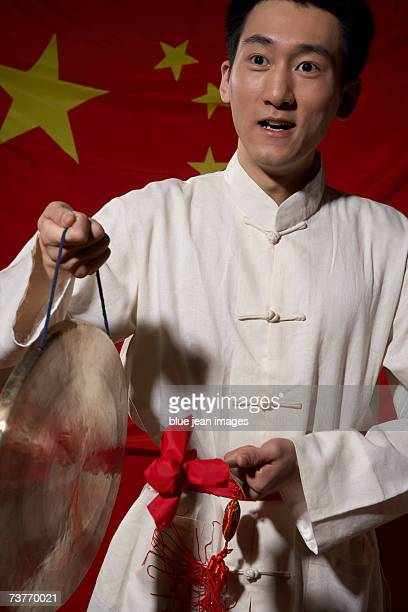 young man in traditional chinese clothes plays a gong in front of a chinese flag. - gong stock photos and pictures