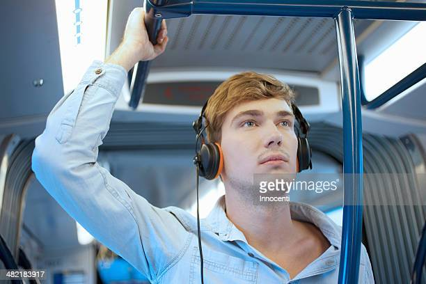 young man in train carriage listening to headphones - railings stock pictures, royalty-free photos & images