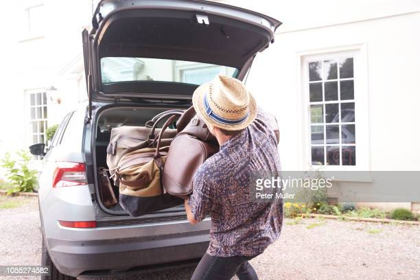 Young man in trilby removing luggage from car boot outside hotel, rear view