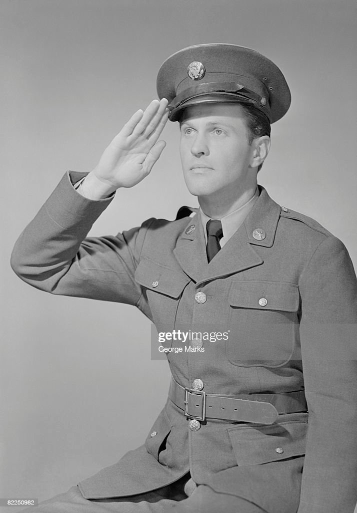 Young man in uniform saluting : Stock Photo