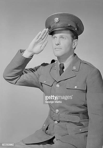 Young man in uniform saluting