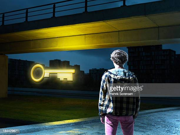 young man in urban environment lookin at key