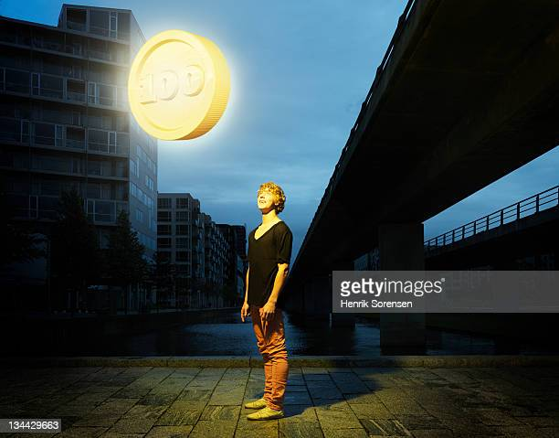 young man in urban environment looking at coin