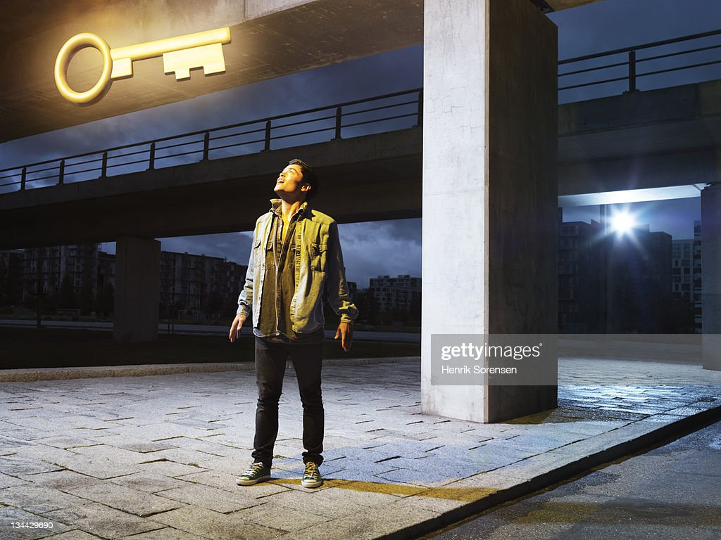 young man in urban environment looking at key : Stock Photo