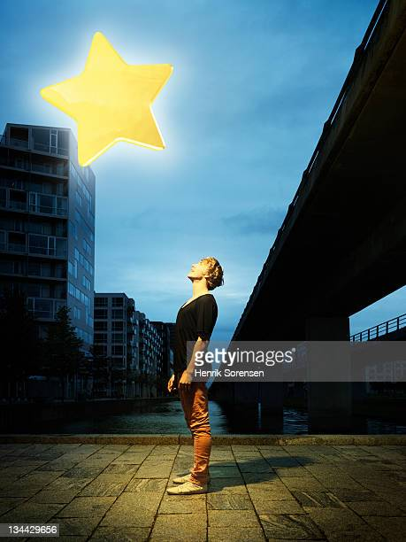 young man in urban environment looking at star