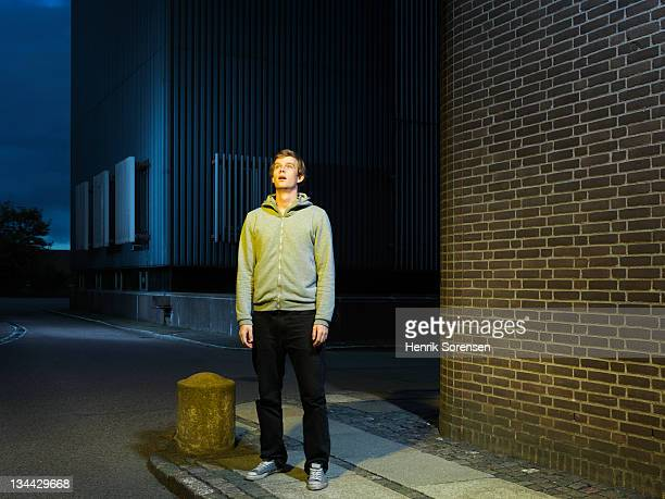 young man in urban environment looking up - staan stockfoto's en -beelden