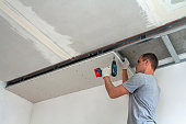 Young man in usual clothing and work gloves fixing drywall suspended ceiling to metal frame using electrical screwdriver on ceiling insulated with shiny aluminum foil. DIY, do it yourself concept.