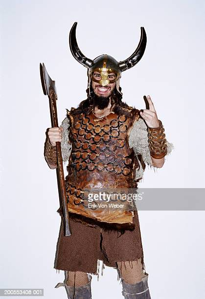 Young man in Viking costume against white background, smiling, portrait