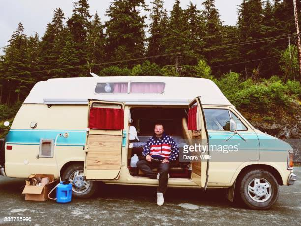 Young man in vintage camper van. Road trip in Alaska USA