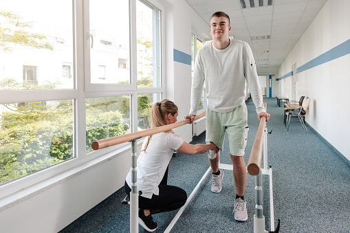 Young man in walking rehabilitation course after a sport injury 1194506777