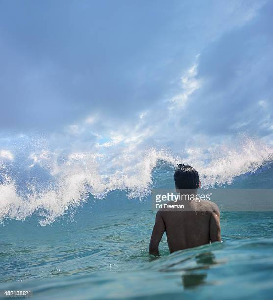 Young Man in Water Facing Big Wave