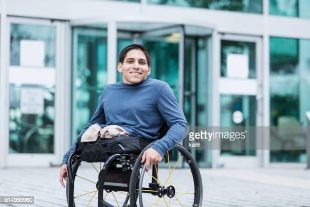 Jeune homme en fauteuil roulant sur le trottoir de la ville