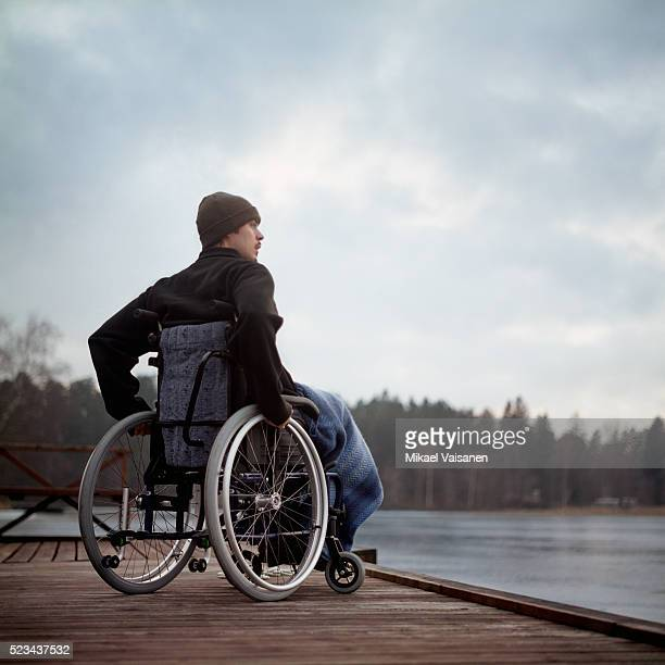 young man in wheelchair on jetty by a lake - differing abilities fotografías e imágenes de stock