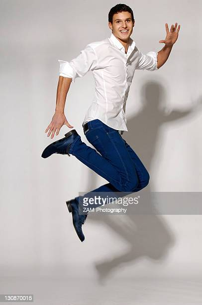 Young man in white shirt and blue jeans jumping