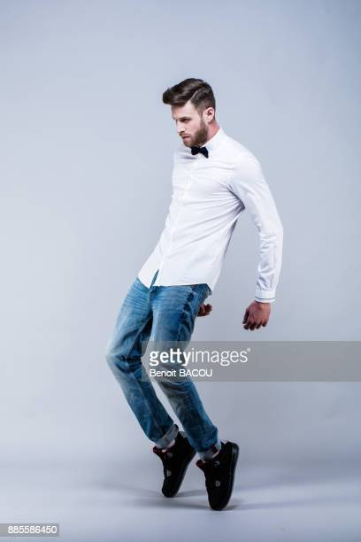 young man in white shirt standing in profile, hands back, on tiptoe - man dancing stock pictures, royalty-free photos & images