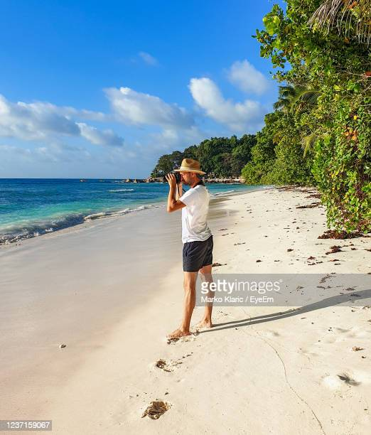 young man in white t-shirt standing on sandy beach, taking photos. - blue shorts stock pictures, royalty-free photos & images
